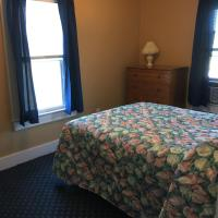 full size bed in bedroom with 2 windows and dresser with lamp