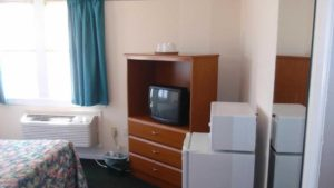 bedroom with double bed kitchenette and tv