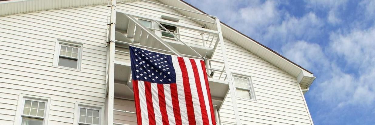 american flag hanging from stairs on exterior of apartment
