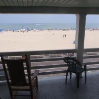 ocean and boardwalk view from balcony with rocking chair and plastic chair