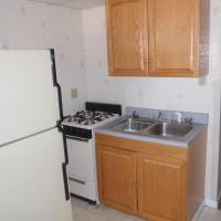 kitchen with fridge, stove, sink, and cabinets