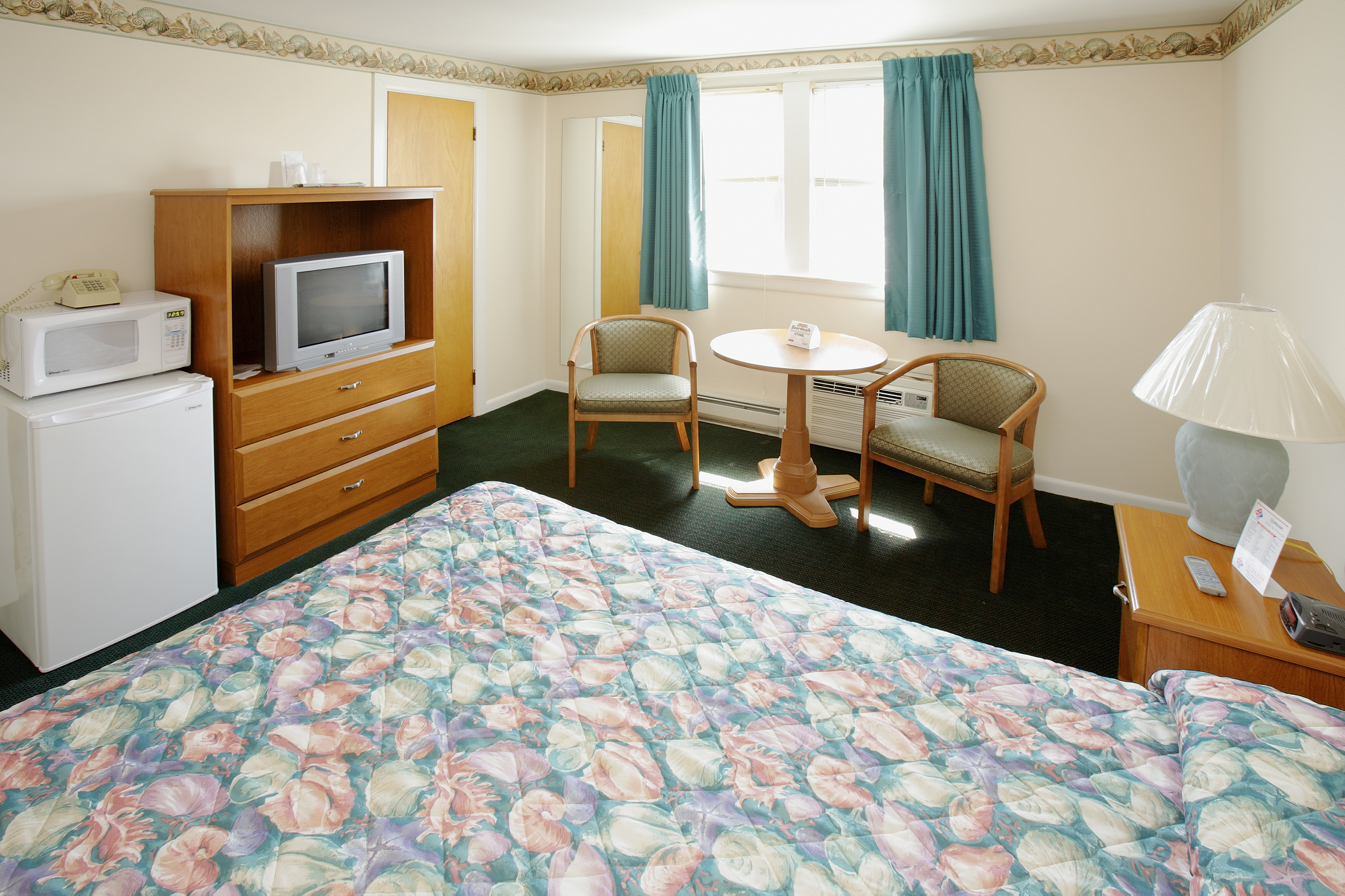bedroom with queen bed, small fridge, microwave and tv