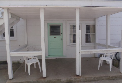 wood covered concrete apartment porch with chairs