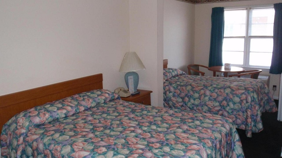 double and twin bed in bedrom with nightstand, seating, and window