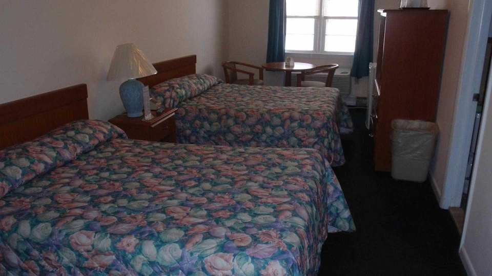 two double beds bedroom with small table and dresser/tv