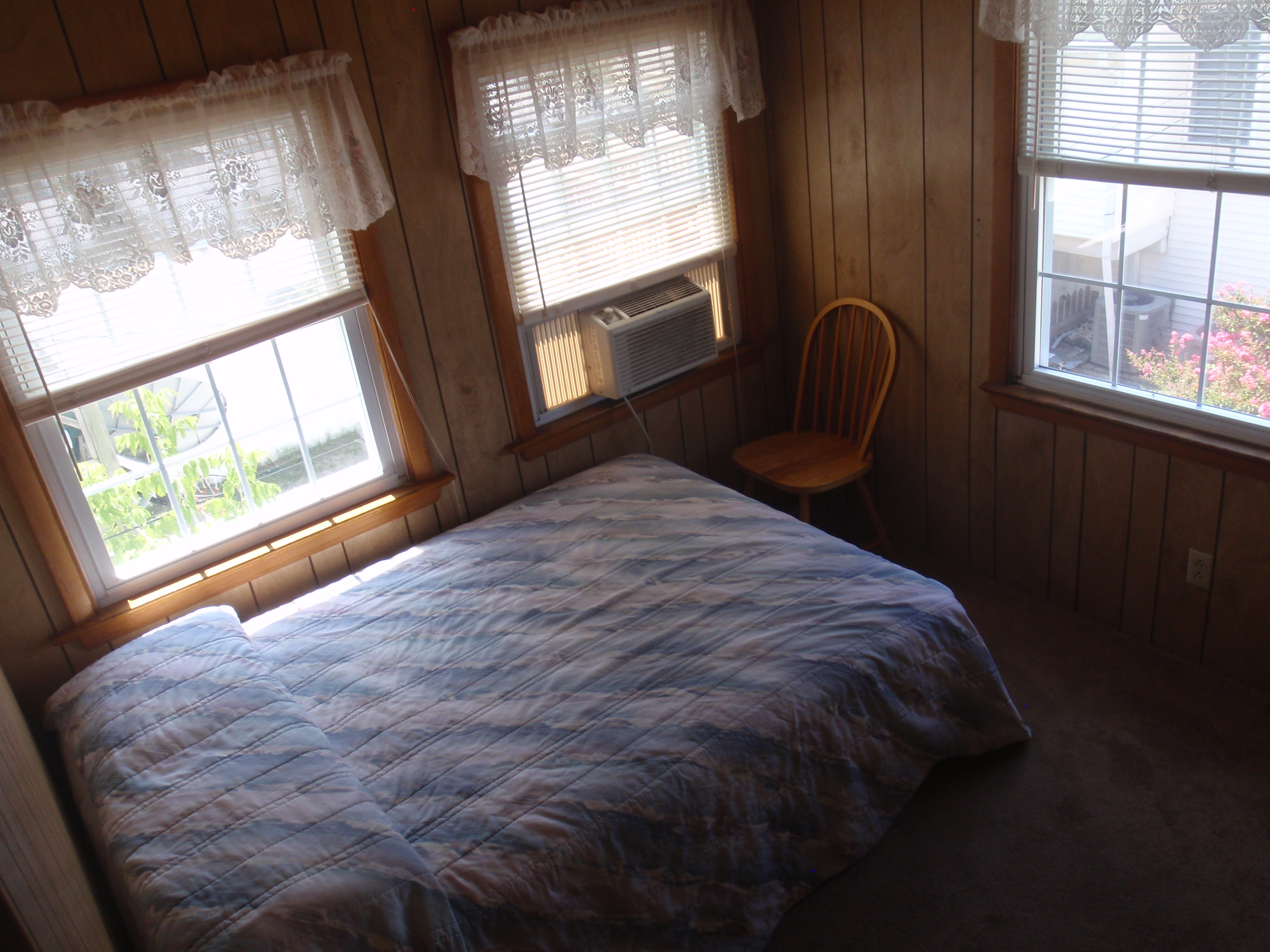 bedroom with full size bed, window a/c unit, and chair